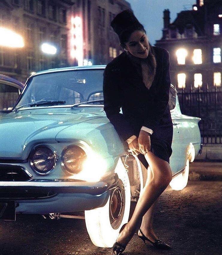Seorang wanita menyesuaikan stokingnya menggunakan cahaya yang dipancarkan oleh ban Goodyear pada malam Oktober 1961.